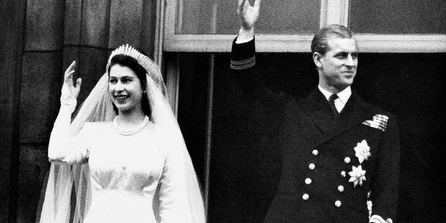 Queen Elizabeth and her husband, the Duke of Edinburgh, greet the crowd on their wedding day, from the balcony of Buckingham Palace in London.