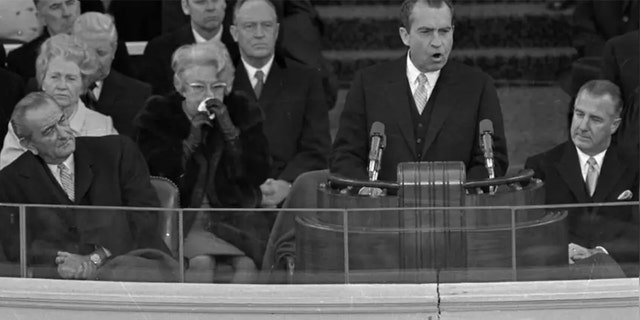 "President Richard M. Nixon dedicates his new administration to the cause of ""peace among nations"" as former President Lyndon Johnson, right, listens to the inaugural speech Jan. 20, 1969 in Washington. Seated at right is Vice President Spiro Agnew and former Vice President Hubert Humphrey."