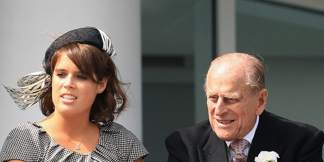 Princess Beatrice of York (L), Princess Eugenie of York (C) and Prince Philip, Duke of Edinburgh (R) watch the action from the royal balcony during the Investec Derby, at the start of the weekend marking the Queen's Diamond Jubilee celebrations, at Epsom Racecourse on June 2, 2012 in Epsom, England.