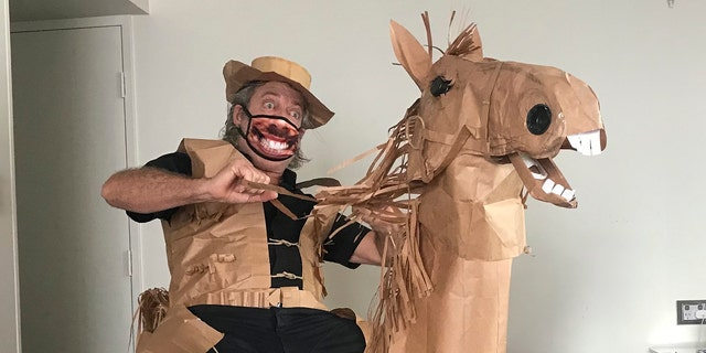 Marriott poses with his paper horse Russell, which he made out of an ironing board, a lamp and brown paper bags. (David Marriott via AP)