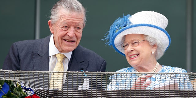 Sir Michael Oswald and Queen Elizabeth II watch the racing from the balcony of the Royal Box as they attend Derby Day during the Investec Derby Festival at Epsom Racecourse on June 4, 2016 in Epsom, England.