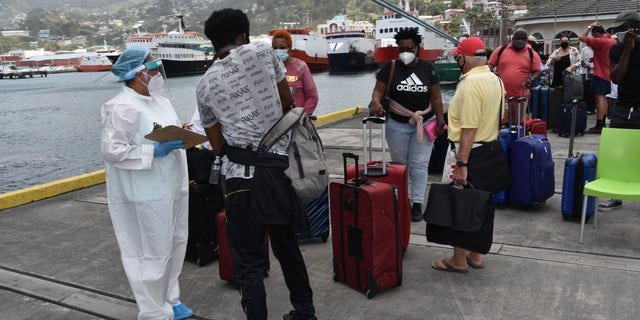 British, Canadian and U.S. nationals wait to board the Royal Caribbean cruise ship Reflection to be evacuated free of charge, in Kingstown on the eastern Caribbean island of St. Vincent, Friday, April 16, 2021. (AP Photo/Orvil Samuel)