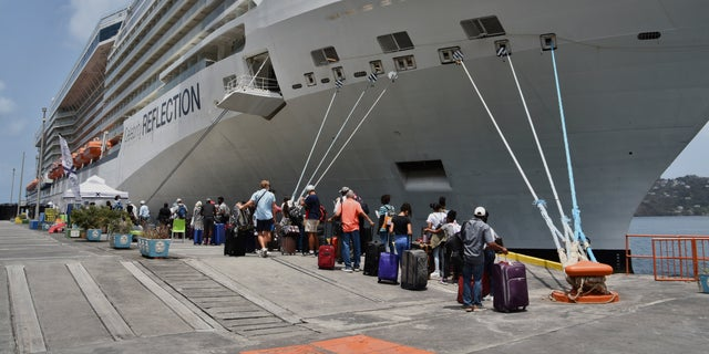 British, Canadian and U.S. nationals line up alongside the Royal Caribbean cruise ship Reflection to be evacuated free of charge, in Kingstown on the eastern Caribbean island of St. Vincent, Friday, April 16, 2021. (AP Photo/Orvil Samuel)