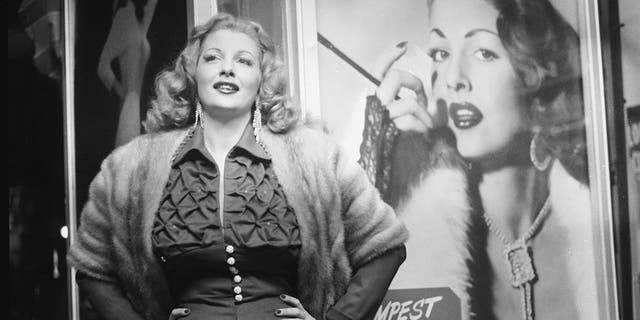 American stripper Tempest Storm poses next to a promotional poster for her burlesque act in front of a theater, 1954. (Getty Images)
