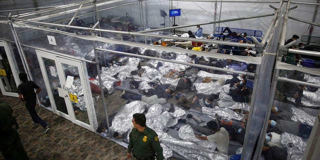 In this March 30, 2021, file photo, young minors lie inside a pod at the Donna Department of Homeland Security holding facility, the main detention center for unaccompanied children in the Rio Grande Valley run by U.S. Customs and Border Protection (CBP), in Donna, Texas. (AP Photo/Dario Lopez-Mills, Pool, File)