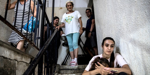 People in Ashdod, Israel take shelter in the stairwell of their apartment building during a siren warning of rockets fired from Gaza to Israel on May 18, 2021.(Associated Press)