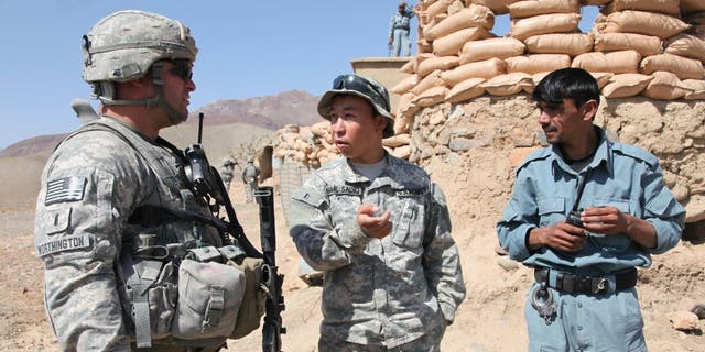 US Army Lieutenant Paul Worthington (left) listens to an interpreter while talking to the Afghan National Police about security issues during a visit to a national police checkpoint in the Jabal Saraj district of Parwan province, Afghanistan on Oct. 8. c. 2010