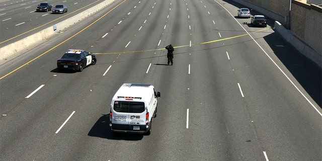 A crime scene investigator photographs the scene while the California Highway Patrol secures the northbound lanes of the 55 Freeway near Chapman Avenue were a 6-year-old boy was fatally shot during apparent road rage incident Friday, 可能 21, 2021 in Orange, 那.