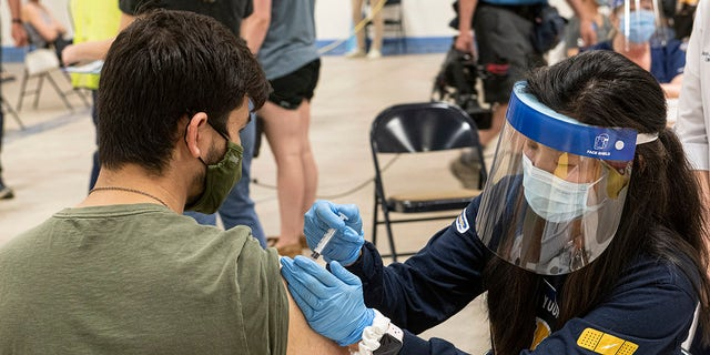 In this April 8, 2021, file photo, Kent State University student Jarrett Woo gets his Johnson & Johnson COVID-19 vaccination from Kent State nursing student Allie Rodriguez in Kent, Ohio. (AP Photo/Phil Long, File)