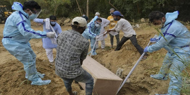 """<strong>Relatives bury body of COVID-19 victim in New Delhi Cemetery, India, Tuesday, May 4, 2021 (AP Photo / Ishant Chauhan)</strong>""""/></source></source></picture></div> <div class="""