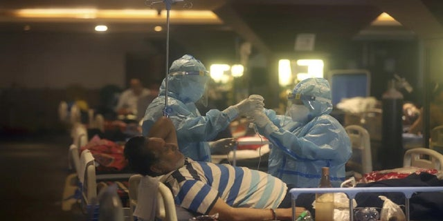 On April 30, 2021, photo by photo, healthcare professionals cared for patients with COVID-19 at a makeshift hospital in New Delhi, India.  (AP photo / file)