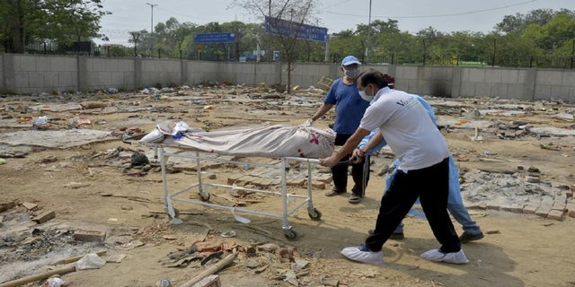 May 1, 2021: Body of a COVID-19 victim is wheeled in a ground that has been converted into a crematorium in New Delhi, India.