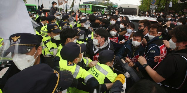 Members of the Korean Confederation of Trade Unions scuffle with police officers during a May Day rally demanding better working conditions and expanding labor rights in Seoul, South Korea, Saturday, May 1, 2021. (AP Photo/Ahn Young-joon)