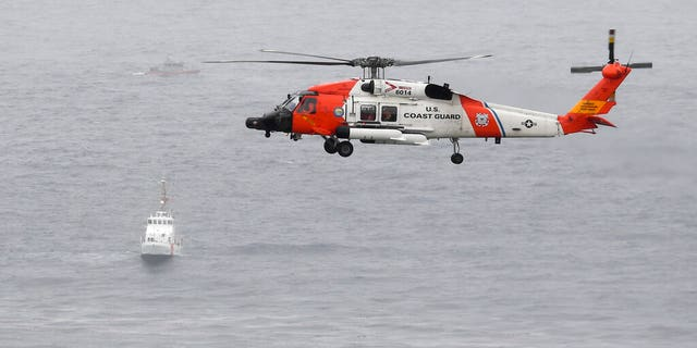 A U.S. Coast Guard helicopter flies over boats searching the area where a boat capsized just off the San Diego coast.