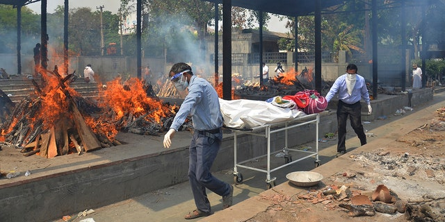 Relatives carry the body of a person who died of COVID-19 as multiple pyres of other COVID-19 victims burn at a crematorium in New Delhi, India on May 1, 2021. (AP Photo/Amit Sharma, File)