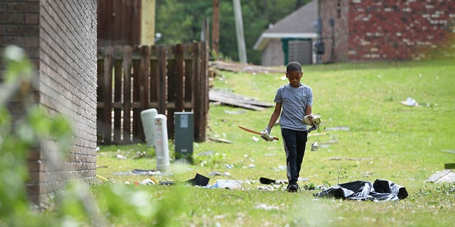 Derrick Pounds Jr., 7, picks up debris around his house on Elvis Presley Drive in Tupelo, Miss., Monday, May 3, 2021. Multiple tornadoes were reported across the state on Sunday. (AP Photo/Thomas Graning)