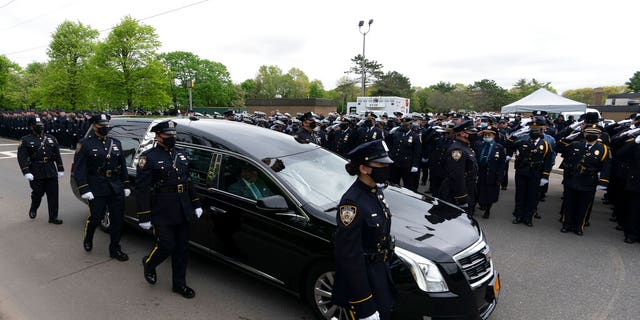 Thousands of police officers line the street as the hearse bearing New York police officer Anastasios Tsakos leaves the St. Paraskevi Greek Orthodox Shrine Church, Tuesday, May 4, 2021, in Greenlawn, N.Y.
