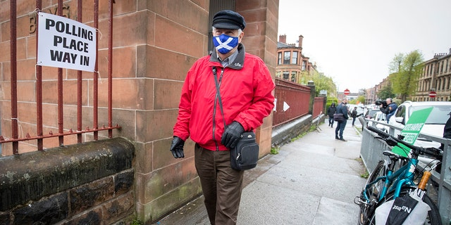 A man wearing a face mask arrives to vote at a polling station in Glasgow, Scotland, Thursday May 6, 2021.