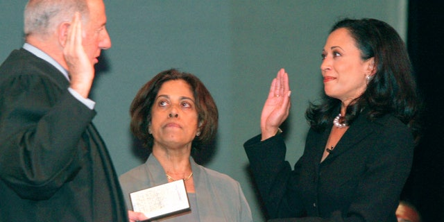 """FILE - In this Jan. 8, 2004, file photo, San Francisco's new district attorney, Kamala Harris, right, receives the oath of office from California Supreme Court Chief Justice Ronald M. George, left, during inauguration ceremonies Thursday, Jan. 8, 2004, in San Francisco, as Harris' mother, Dr. Shyamala Gopalan, holds a copy of """"The Bill of Rights."""" (AP Photo/George Nikitin, File)"""