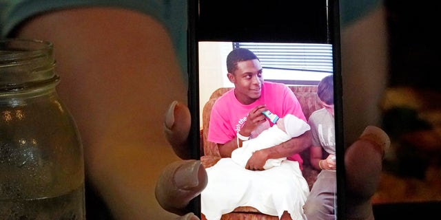 Alexis Rankin holds a 2018 cell phone photograph of her former boyfriend Willie Jones Jr., holding their newborn son, as she recalls the events of February 8, 2018, when Jones was discovered hanging from a tree in the yard of Rankin's family home shortly after arriving there with Rankin. The sheriff's department and the Mississippi Bureau of Investigation, both ruled the death a suicide. However, a Jackson-area judge in April awarded close to $11.4 million to Jones' family in a civil suit claiming wrongful death, alleging that Rankin's stepfather, Harold O'Bryant, Jr., either killed Jones or failed to prevent him from killing himself. (AP Photo/Rogelio V. Solis)
