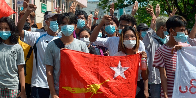 """Anti-coup protesters hold the flag of the National League for Democracy party of ousted Myanmar leader Aung San Suu Kyi, while others flash the three-fingered salute during a """"flash mob"""" rally in Bahan township in Yangon, Myanmar, Sunday, May 9, 2021. (AP Photo)"""