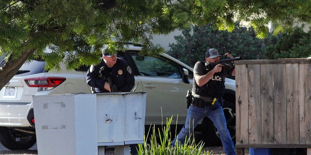 Officials target an apartment across from Camilla Court on Monday May 10, 2021 in San Luis Obispo, California.  Police said two police officers were shot while serving a search warrant and the suspect died.  (David Middlecamp / The Tribune (by San Luis Obispo) via AP)