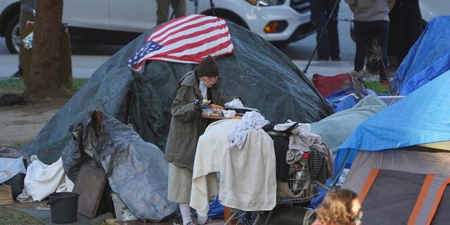 In this March 24 file photo, a woman eats at her tent at the Echo Park homeless encampment at Echo Park Lake in Los Angeles. (AP Photo/Damian Dovarganes, File)