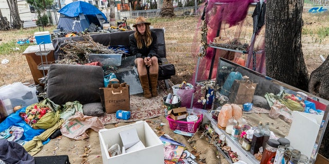 Dawn Woodward, 39, who is homeless and originally from Arizona, sits outdoors in a homeless camp on the side of the CA-101 highway in Echo Park neighborhood in Los Angeles. (AP Photo/Damian Dovarganes)