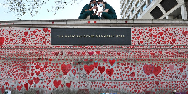 FILE - In this Tuesday, April 27, 2021 file photo, nurses from the nearby St Thomas' hospital sit atop the National Covid Memorial Wall in London.