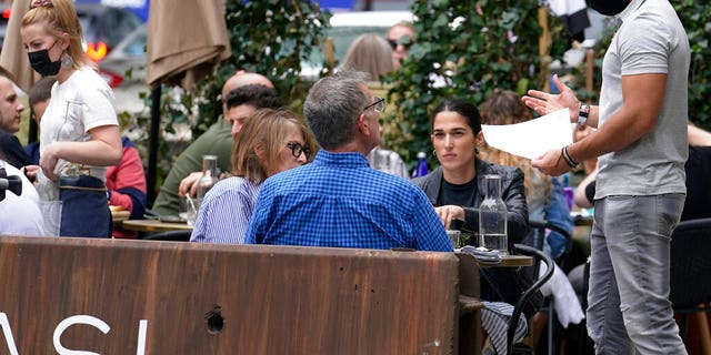 FILE: Patrons at a sidewalk cafe are seated without masks in Boston.