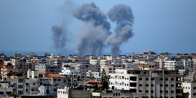 Smoke rises following Israeli airstrikes on a building in Gaza City, Thursday, May 13, 2021. Israeli airstrikes killed multiple senior Hamas military figures Wednesday and toppled a pair of high-rise towers housing Hamas facilities. (AP Photo/Hatem Moussa)