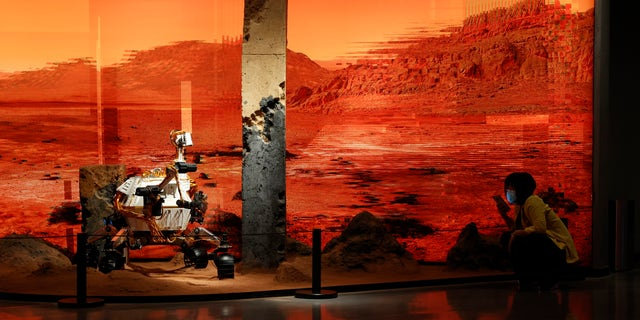 A woman wearing a mask talks on her phone near an exhibition depicting a rover on Mars in Beijing on Friday, May 14, 2021. China says its Mars probe and accompanying rover landed on the red planet. (AP Photo/Ng Han Guan)