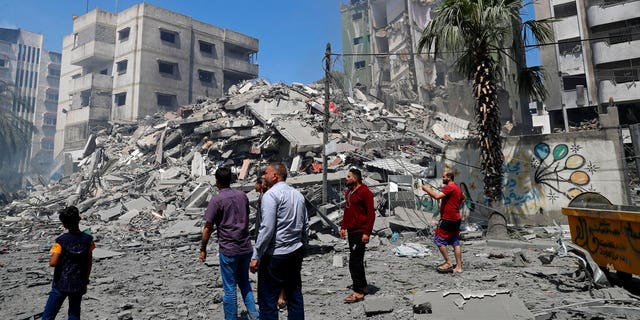 People insect the rubble of the Yazegi residential building that was destroyed by an Israeli airstrike, in Gaza City, Sunday, May 16, 2021.