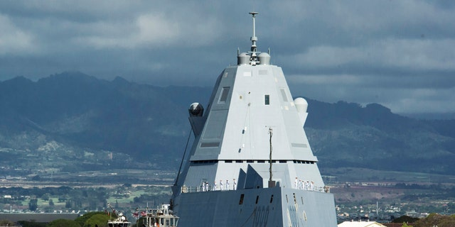FILE - The guided missile destroyer USS Zumwalt is assisted by a tugboat at Joint Base Pearl Harbor-Hickam, in this Tuesday, April 2, 2019, file photo, in Honolulu. The electric-drive, angular Zumwalt was commissioned into service, but its 155mm advanced gun system is being scrapped because its munitions are too expensive. (Craig T. Kojima/Honolulu Star-Advertiser via AP, File)