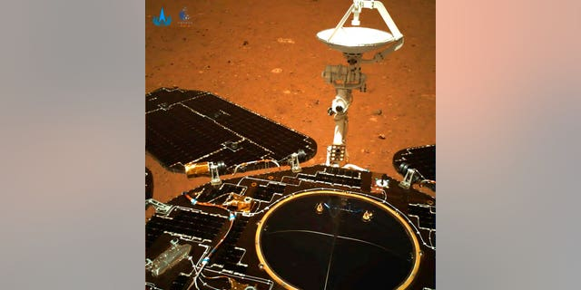 The rover's solar panels and antenna are deployed as the rover sits on its lander on the surface of Mars.