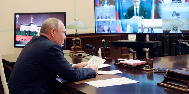 """Russian President Vladimir Putin chairs a meeting of Pobeda (Victory) organising committee via teleconference at the Novo-Ogaryovo residence outside Moscow, Russia, Thursday, May 20, 2021. Russian President Vladimir Putin alleged Thursday that some of the country's foreign foes dream about biting off pieces of the country's vast territory, warning that Moscow would """"knock their teeth out"""" if they ever try. (Sergei Ilyin, Sputnik, Kremlin Pool Photo via AP)"""