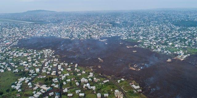 Lava da erupção do Monte Nyiragongo corta Buhene ao norte de Goma, Congo, segunda-feira, 24 de maio de 2021. Moradores voltaram para casas destruídas em busca de entes queridos desaparecidos nos arredores de Goma quando autoridades depois do grande vulcão pediram vigilância em meio a pequenos tremores estourou no sábado, 22 de maio de 2021.  Depois de escurecer, o Monte Nyiragongo enviou fluxos de lava para as aldeias com poucos avisos, matando pelo menos 15 pessoas no caos e destruindo mais de 500 casas.  (AP Photo / Justin Kabumba)