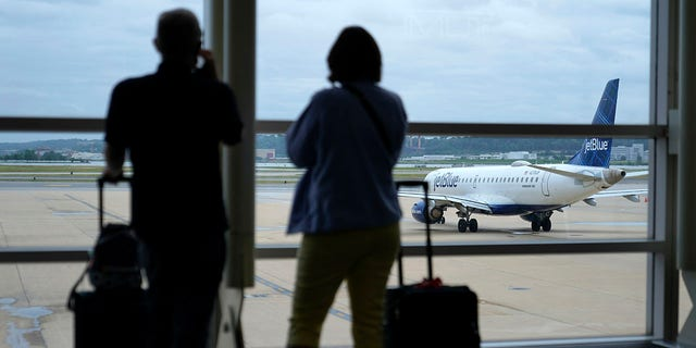 Travelers watch a JetBlue Airways aircraft taxi away from a gate at Ronald Reagan Washington National Airport ahead of Memorial Day weekend, martedì, Maggio 25, 2021, in Arlington, volontà. (AP Photo / Patrick Semansky)