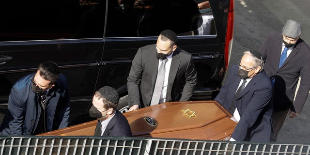 A coffin is carried by members of the Jewish community at the morgue of Verbania Hospital, in Verbania, Italy, Wednesday, May 26, 2021. A prayer ceremony for the Jewish victims took place in Verbania Wednesday morning, before the bodies of the dead were released to return to their homes for funerals and burials. Three people were arrested following a cable car disaster that killed 14 people, after the lead cable apparently snapped and the cabin careened back down the mountain until it pulled off the line and crashed to the ground. (AP Photo/Luca Bruno)
