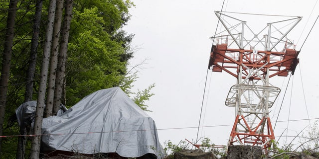 The wreckage of a cable car after it collapsed near the summit of the Stresa-Mottarone line in the Piedmont region, northern Italy, Wednesday, May 26, 2021. Police have made three arrests in the cable car disaster that killed 14 people after an investigation showed a clamp, placed on the brake as a patchwork repair effort, prevented the brake from engaging after the lead cable snapped. (AP Photo/Luca Bruno)