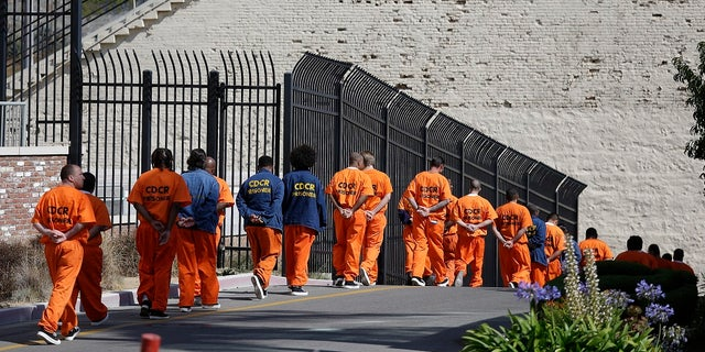 In this Aug. 16, 2016, file photo, a row of general population inmates walk in a line at San Quentin State Prison in San Quentin, Calif. Three-quarters of California's district attorneys sued the state Wednesday in an attempt to block emergency rules that expand good conduct credits and could eventually bring earlier releases for tens of thousands of inmates. (AP Photo/Eric Risberg, File)
