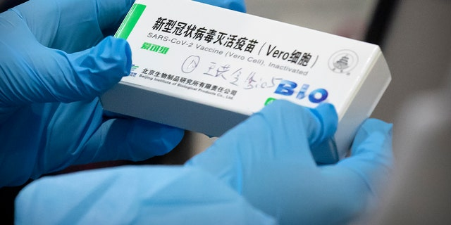 A medical worker holds a package for a Sinopharm vaccine at a vaccination facility in Beijing on Jan. 15, 2021. Two vaccines made by China's Sinopharm appear to be safe and effective against COVID-19, according to a study published in a medical journal. Scientists have been waiting for more details about the two vaccines, even though they already are being used in many countries and one recently won the backing of the World Health Organization. (AP Photo/Mark Schiefelbein)