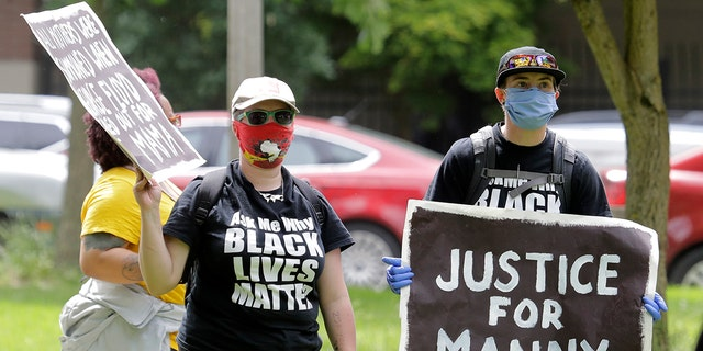 """A protester holds a sign that reads """"Justice for Manny"""" in this June 5, 2020 file photo in Tacoma, Wash., during a protest against police brutality. (Associated Press)"""