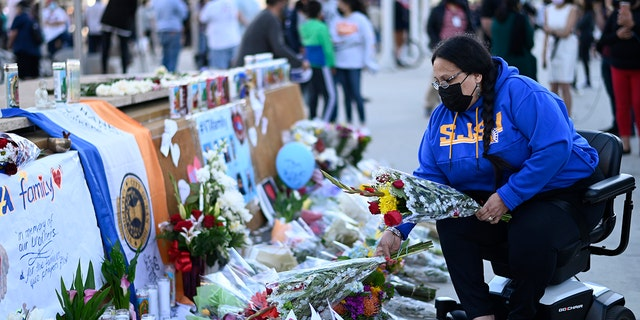 Diana Carreras places flowers at a vigil at City Hall in San Jose, 加利福尼亚州, 星期四, 可能 27, 2021, in honor of the multiple people killed when a gunman opened fire at a rail yard the day before. (美联社)