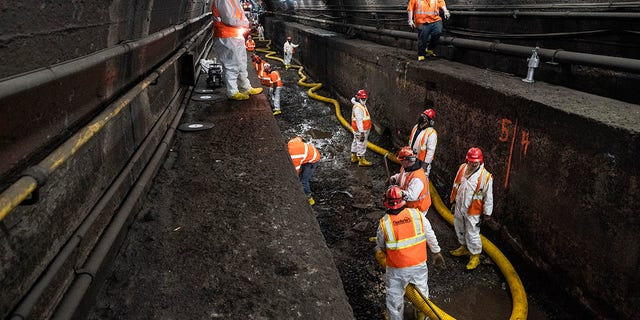 FILE - この3月に 20, 2021 ファイル写真, Amtrak workers perform tunnel repairs to a partially flooded train track bed, in Weehawken, N.J. (AP Photo/John Minファイルlo, File)