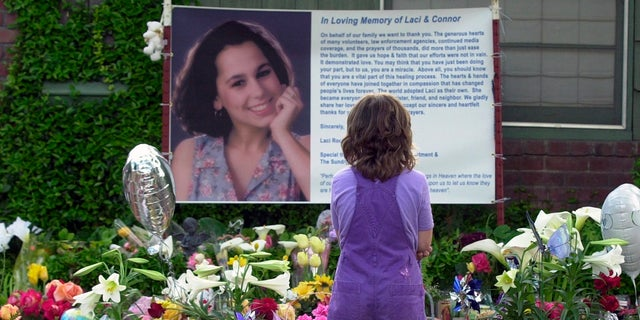 In this April 21, 2003 file photo, Sarah Kellison stands in front of a memorial in honor of Laci Peterson outside the house Laci shared with her husband Scott Peterson in Modesto, Calif. (AP Photo/Marcio Jose Sanchez, File)