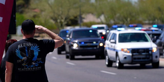 People line the streets as the body of Chandler Police Officer Christopher Farrar, killed in the line of duty last Thursday, is escorted during a large multi-jurisdiction police procession Friday, May 7, 2021, in Chandler, Ariz. Officer Farrar was struck by a suspect in a stolen vehicle after a long police chase. (AP Photo/Ross D. Franklin)