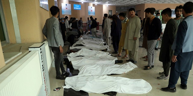 Afghan men try to identify the dead bodies at a hospital after a bomb explosion near a school west of Kabul, Afghanistan, Saturday, May 8, 2021. (Associated Press)