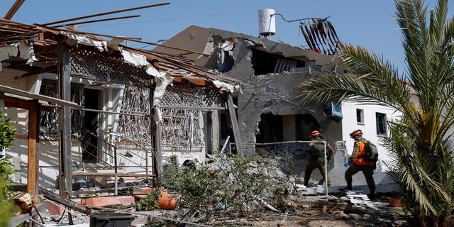 Israeli soldiers inspect a house damaged by a missile fired from the Gaza Strip in the southern Israeli city of Ashkelon on Tuesday. (AP)