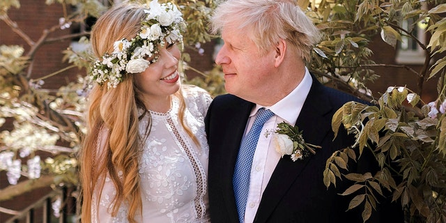 In this photo released on Sunday, May 30, 2021, beside Downing Road.  Prime Minister Boris  England's Johnson and Carrie Johnson are photographed together in the park at 10 Downing Street after their wedding on Saturday. Boris Johnson and fiance Carrie Symonds are now engaged.  According to an announcement from his Downing Street office, they were married on Saturday, May 29, in a small private ceremony in London. (Rebecca Fulton/Downing Street via AP)